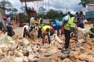 Les jeunes triant le plastique sec pour la fabrication des pavés